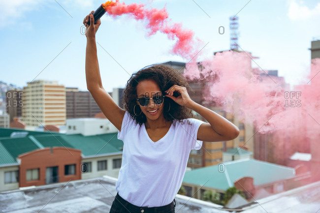 Front view of a young African-American woman wearing a white shirt and eyeglass smiling while holding a smoke maker producing red smoke on a rooftop with a view of buildings