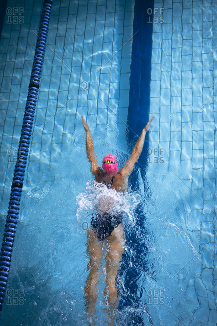 High angle view of a Caucasian woman wearing a pink swimming cap and goggles doing a butterfly stroke in a swimming pool