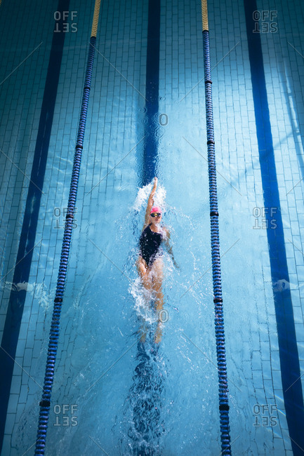 High angle view of a Caucasian woman wearing a pink swimming cap and goggles doing a back stroke in a swimming pool