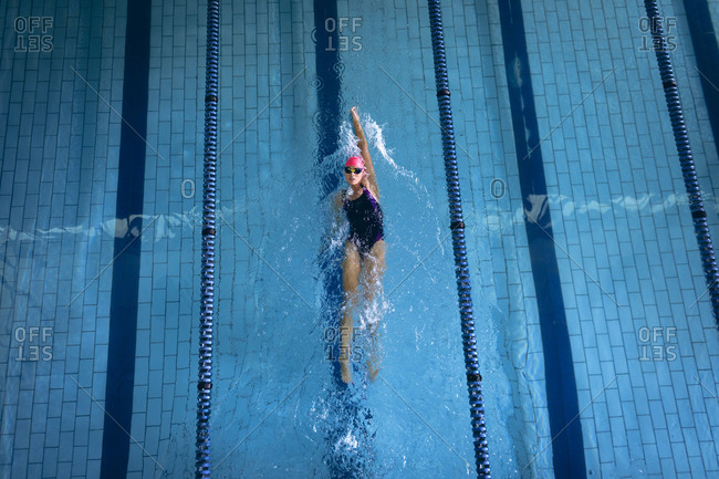 High angle view of a Caucasian woman wearing a swimsuit and a pink swimming cap doing back stroke in the swimming pool