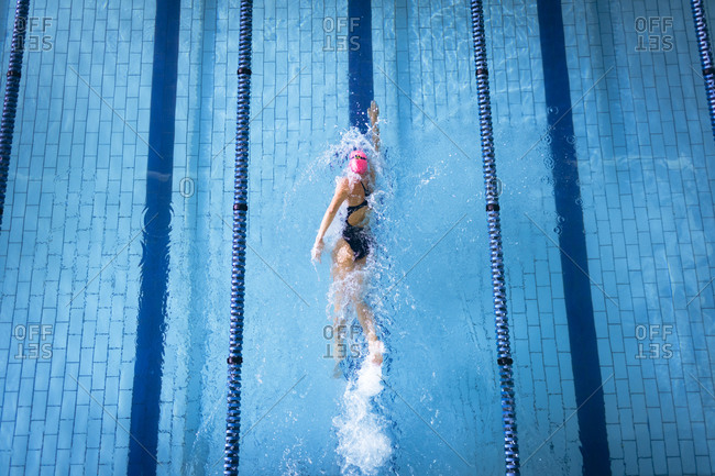 High angle view of a Caucasian woman wearing a swimsuit and a pink swimming cap doing freestyle stroke in the swimming pool