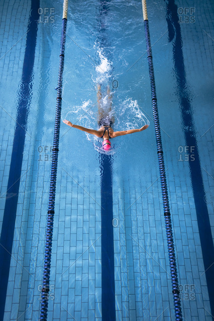 High angle view of a Caucasian woman wearing a swimsuit and a pink swimming cap doing butterfly stroke in the swimming pool