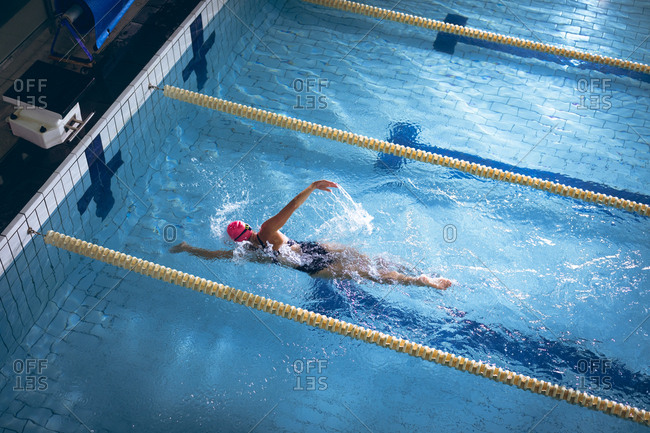 High angle view of a Caucasian woman wearing a swimsuit and a pink swimming cap doing a freestyle stroke in the swimming pool