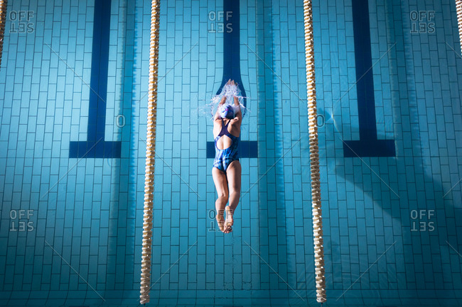 High angle view of an African-American woman wearing a swimsuit and a blue swimming cap diving in the swimming pool