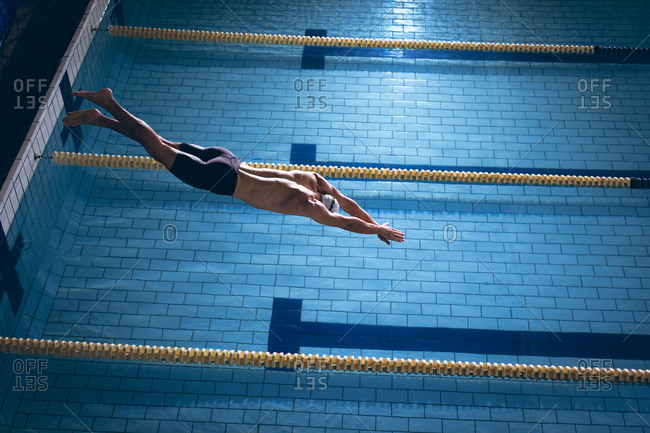 High angle view of a male Caucasian swimmer wearing a white swimming cap diving in the swimming pool