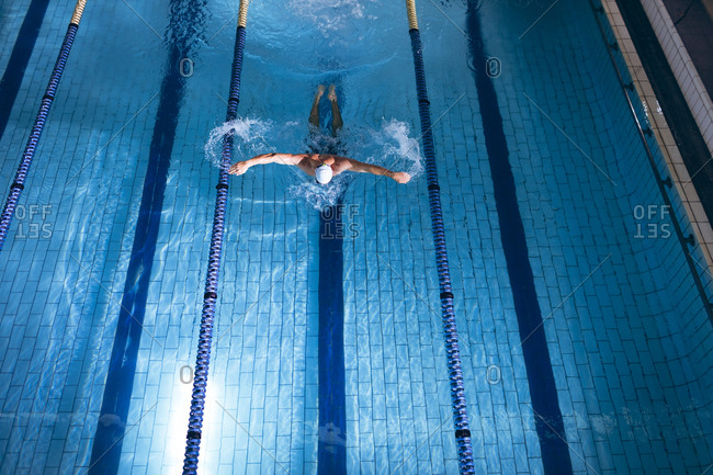 High angle view of a male Caucasian swimmer wearing a white swimming cap doing a butterfly stroke in the swimming pool