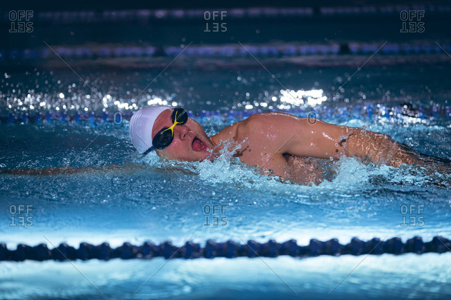 Side view of a male Caucasian swimmer wearing a white swimming cap and goggles doing a freestyle stroke in the swimming pool