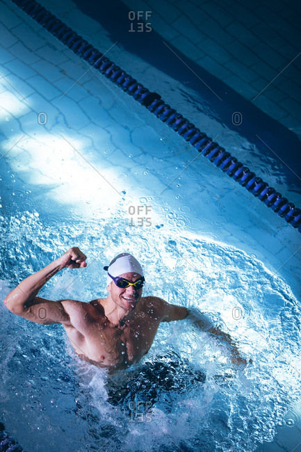 High angle view of a male Caucasian swimmer wearing a white swimming cap and goggles with one fist up smiling while standing in the swimming pool