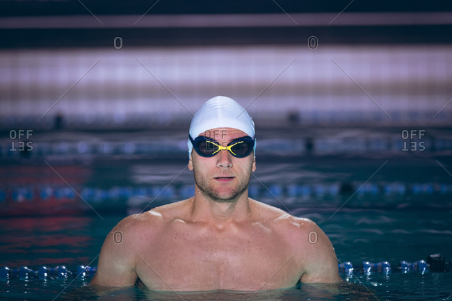 Front view of a male Caucasian swimmer wearing a white swimming cap and goggles while standing in the swimming pool