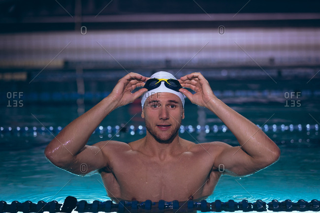 Front view of a male Caucasian swimmer holding the goggles on his white swimming cap while standing in the swimming pool