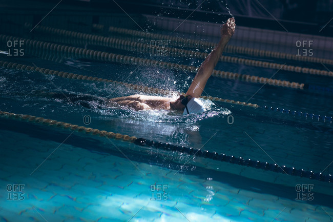 Side view of a male Caucasian swimmer wearing a white swimming cap and goggles doing a back stroke in the swimming pool