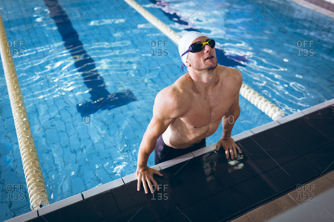 Front view of a male Caucasian swimmer wearing a white swimming cap and goggles lifting body up by the side of the swimming pool