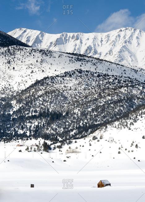 Fresh winter snows and cabin with Sierra Nevada in background, Eastern Sierra, California
