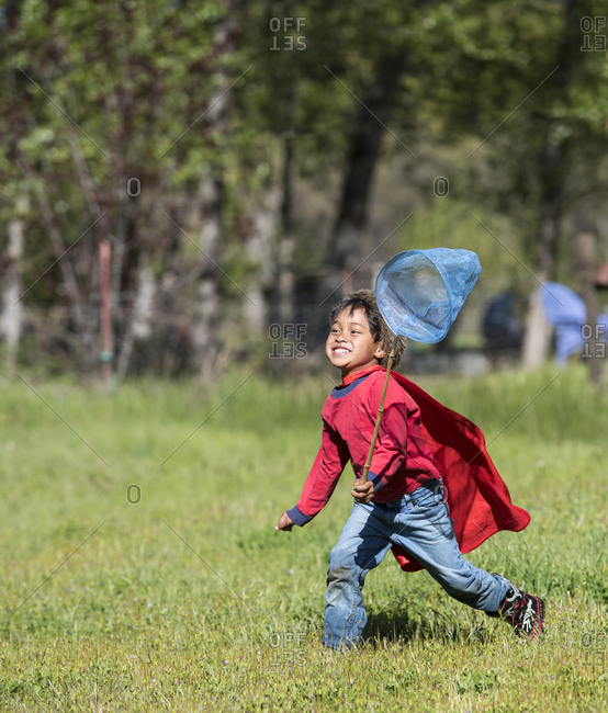 Young Asian Boy Chasing Butterflies On Grassy Landscape