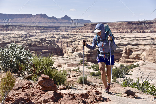 Female backpacker hiking through Canyonlands National Park, Moab, Utah, USA