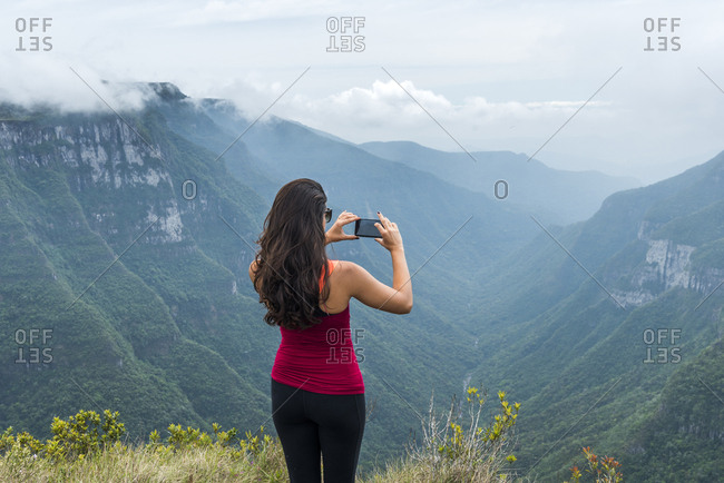 Young woman photographing in Canion Fortaleza, Cambara do Sul, Rio Grande do Sul, Brazil