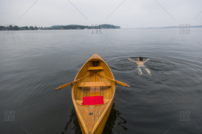 A young man swims next to a small antique wooden row boat in the St. Lawrence River in upstate New York's 1000 Islands.