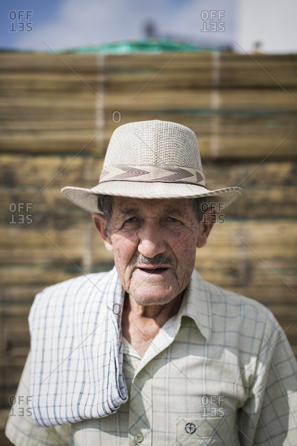 A portrait of an older Colombian man looking at the camera and wearing a traditional hat.