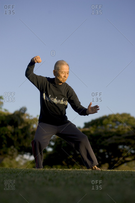 United States, Hawaii, Honolulu - June 30, 2005: An elderly man, age 89, performs his daily Tai Chi regimen at Magic Island park in Honolulu.