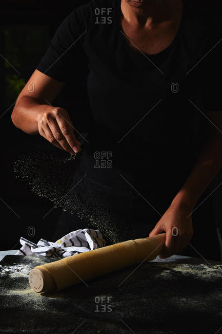 Person sprinkling flour on dough for pasta