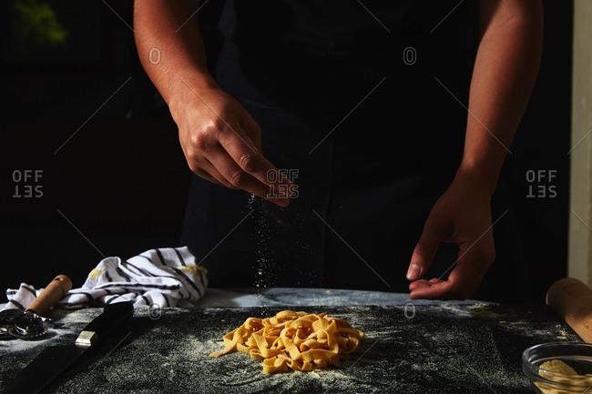 Person sprinkling flour over handmade pasta