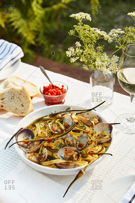Fettuccine with mussels dish served on outdoor table