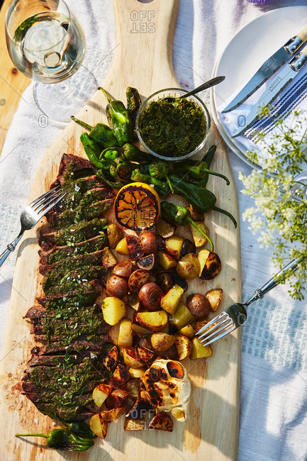 Steak, potatoes and jalapenos served on outdoor table