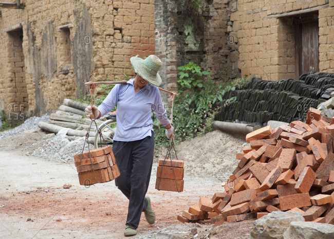 Guilin, China - September 27, 2009: Female construction worker carrying heavy load of bricks for building homes