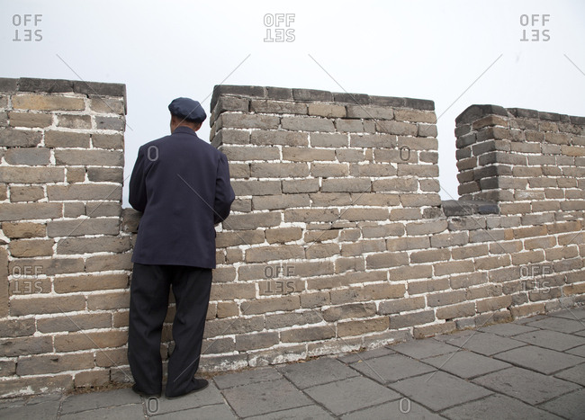 Old man wearing a Mao suit looking out form The Great Wall, Beijing, China