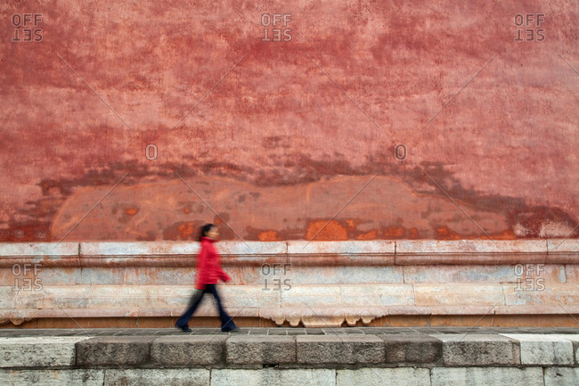 Chinese woman wearing a red jacket walking by a red wall at The Forbidden city palace complex, Beijing, China