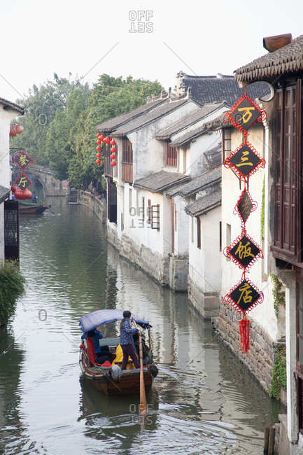 Shanghai, China - October 28, 2010: Tourists taking a ride on small boat in canal in Zhouzhuang Watertown