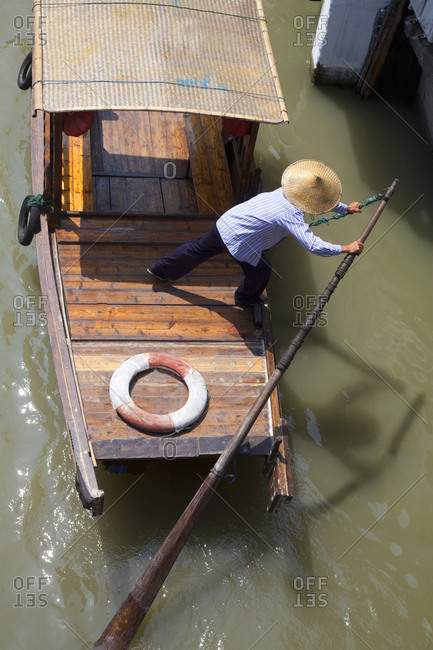 Overhead view of tourists taking a ride on small boat in canal in Zhouzhuang Watertown, Shanghai, China
