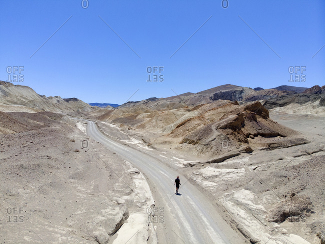 Tourist taking photographs on desert road, Death Valley, California