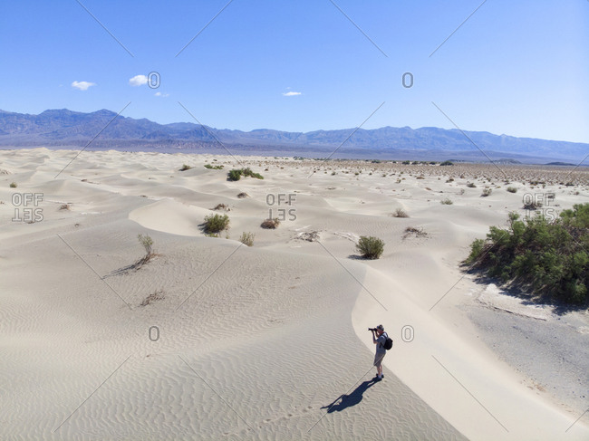 Man hiking on sand dunes and taking photographs, Death Valley, California