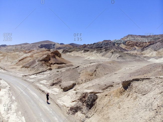 Man taking photographs on desert road, Death Valley, California