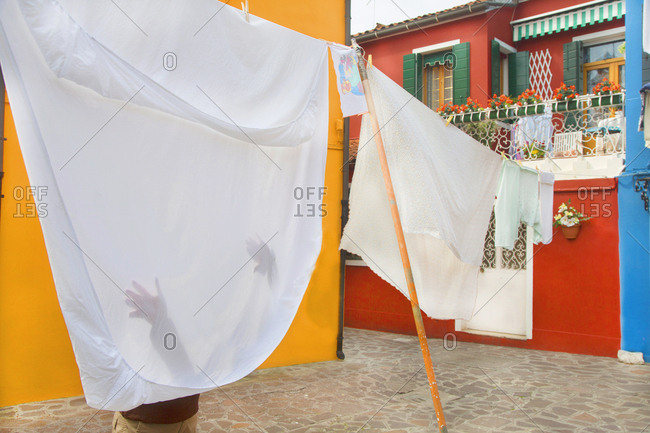 Venice, Italy - April 1, 2013: Woman's hands touching washing hanging on clothes line on Burano Island