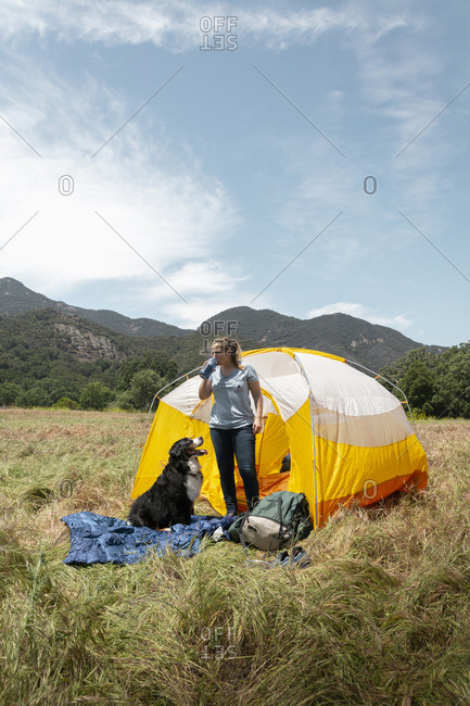 Woman drinking while standing by dog at campsite