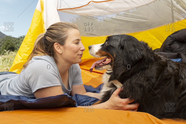 Woman lying with dog in tent at campsite