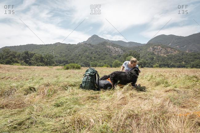 Woman kissing dog on grassy landscape against sky