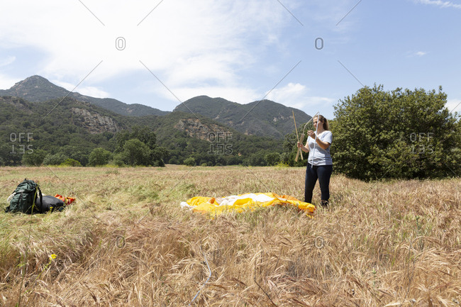Woman disassembling tent on grass at campsite against sky