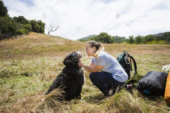Woman stroking dog on grassy landscape against sky