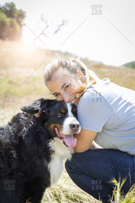 Portrait of smiling woman with dog on sunny day
