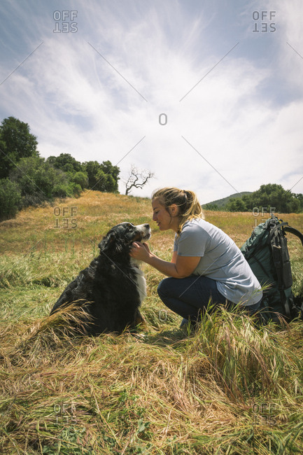 Full length side view of woman with dog on grass