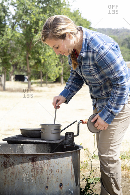 Woman cooking at campsite on sunny day