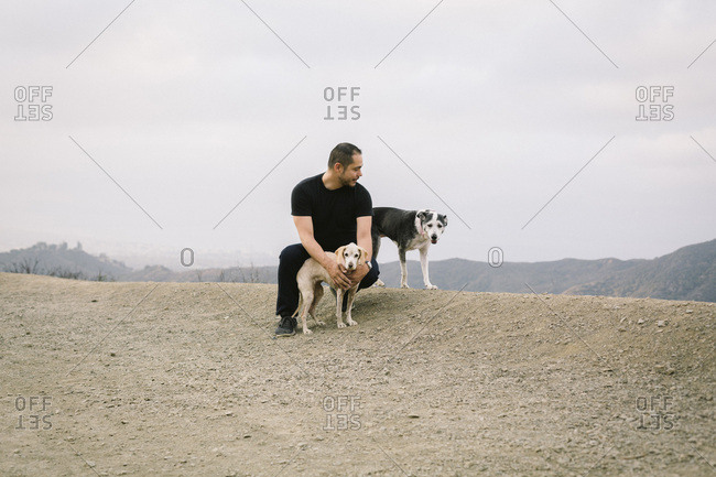 Full length of man crouching by dogs against sky