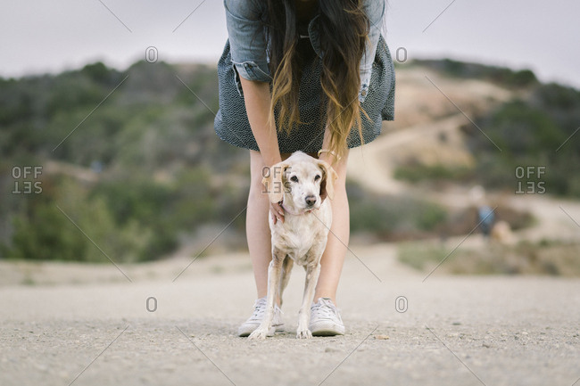 Low section of woman standing with dog on dirt road
