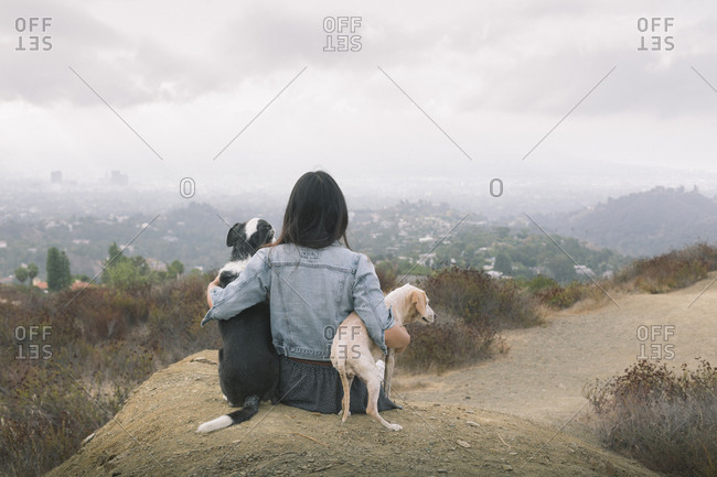 Rear view of woman sitting dogs on mountain
