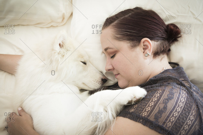 High angle view of woman sleeping with white dog on bed at home