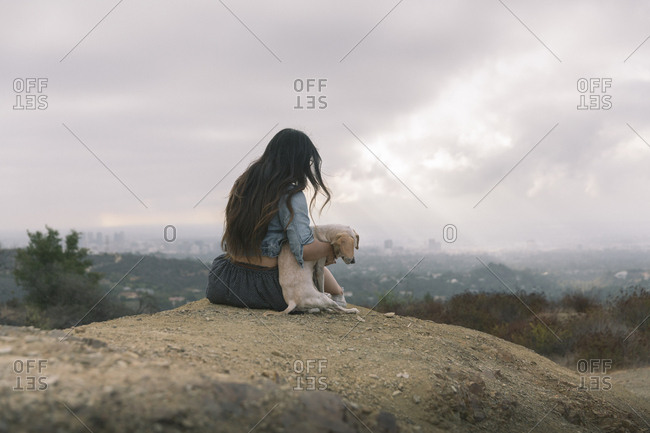 Rear view of woman sitting puppy on mountain