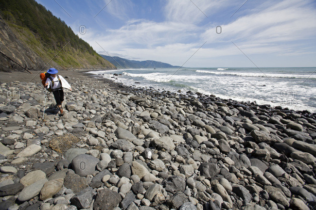 One man backpacks and surfs on The Lost Coast, California.